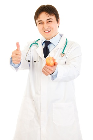 Smiling  medical doctor holding apple and showing thumbs up gesture   photo