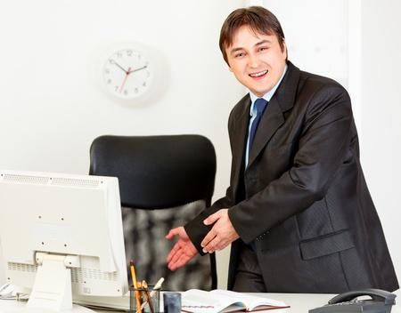 invitando: Hombre de negocios modernos amistosa invitando a sentarse en la silla de Oficina  Foto de archivo
