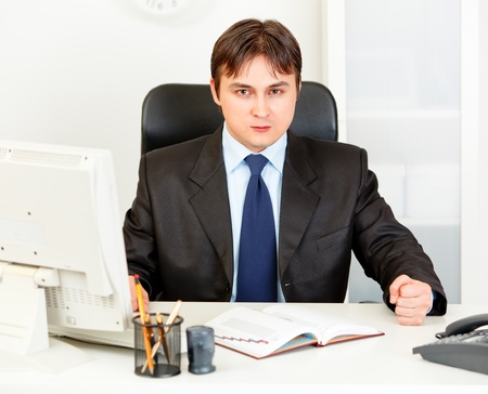 dissatisfied: Dissatisfied modern business man banging fist on table  Stock Photo
