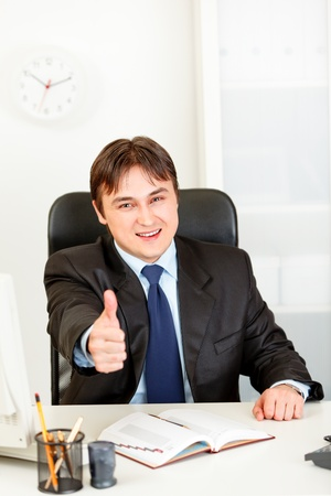 Pleased modern business man sitting at office desk and showing thumbs up gesture  photo