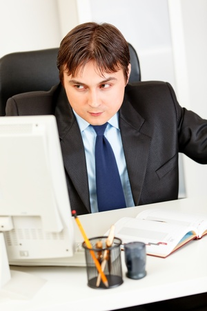 Alert modern businessman sitting at office desk and looking at the computer  photo