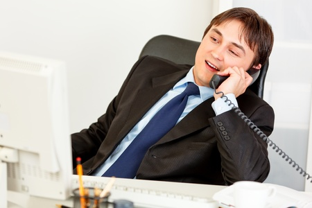 Pleased businessman sitting at office desk and talking on the phone Stock Photo - 8847920