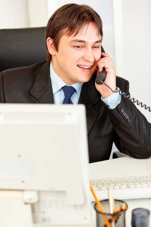 Successful businessman sitting at office desk and talking on phone