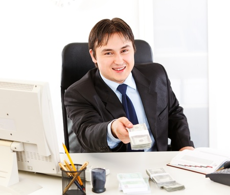 Smiling  business man sitting at office desk and giving dollar pack Stock Photo - 8847784