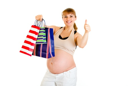 Happy pregnant woman holding shopping bags and showing thumbs up gesture   photo