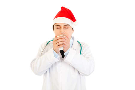 heal new year: Medical doctor in Santa hat enjoying cup of hot coffee   Stock Photo