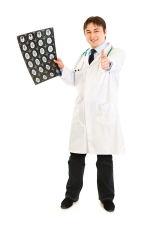 Smiling medical doctor holding tomography and showing thumbs up gesture  photo