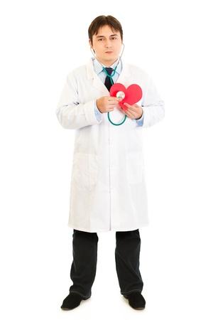 Authoritative medical doctor holding stethoscope on a heart paper shape  Stock Photo - 8848290