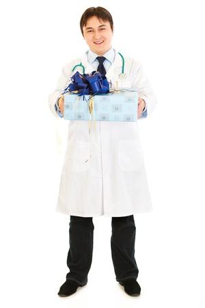 doctor holding gift: Smiling medical doctor holding present