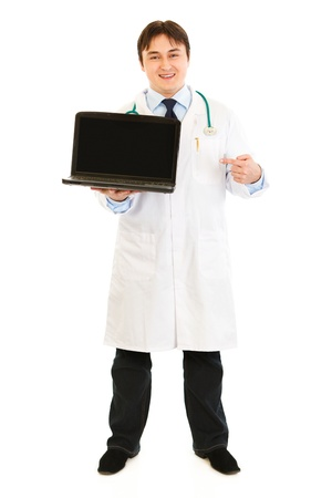 Smiling  doctor pointing finger on a blank screen laptop  photo