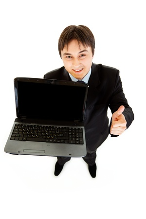 Smiling businessman holding laptops blank screen and showing  thumbs up gesture  isolated on white  photo