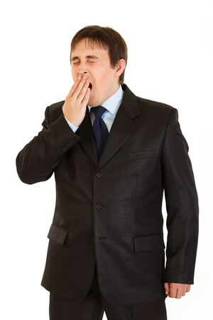 yawning: Tired young  businessman yawning isolated on white