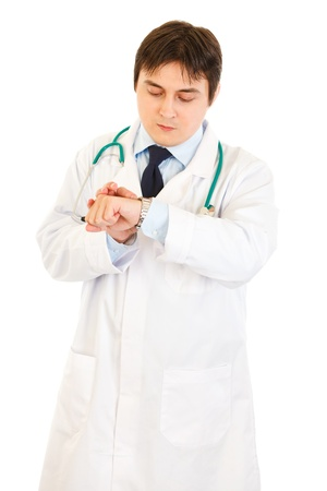 Concentrated medical doctor looking at  clock  isolated on white  photo