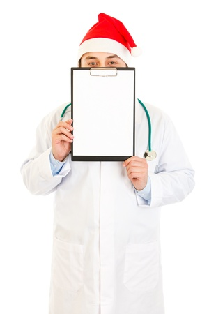 Medical doctor in Santa hat holding blank clipboard isolated on white  photo