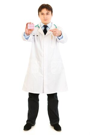 Serious medical doctor pointing finger at pack of pills isolated on white