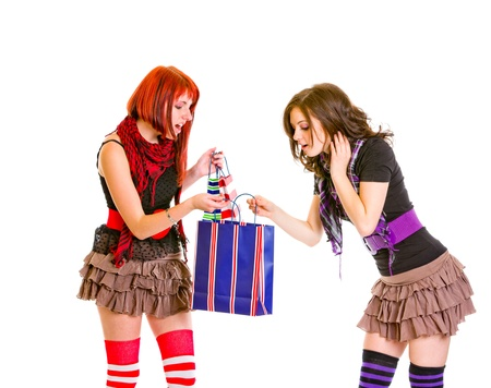 interrogatively: Curious charming girls looking at shopping bag isolated on white  Stock Photo