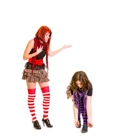 malcontent: Girl trying to talk with not listening her tying shoelaces girlfriend isolated on white  Stock Photo