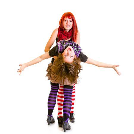 jaunty: Dos amigas jaunty abrazando gracioso aislado en blanco