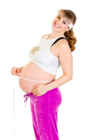 belle femme enceinte: Happy belle femme enceinte mesurer son ventre isol� sur fond blanc