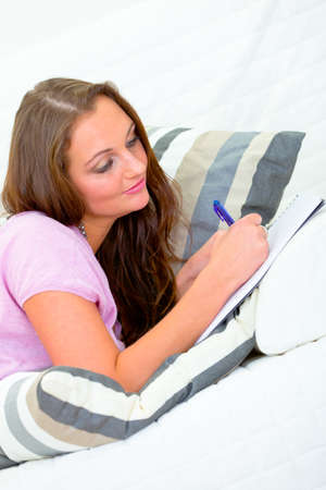 Pensive pretty woman lying on sofa at home and writing in notebook