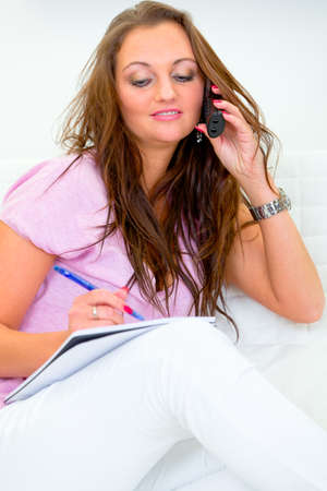 centrality: Concentrated pretty woman talking on phone and making notes in pad
