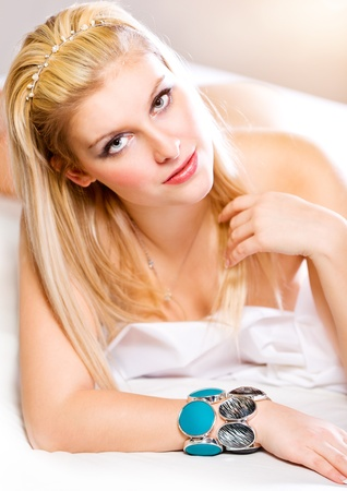 Portrait of sensual young lady with long straight blonde hair lying in bed. Retouched  photo