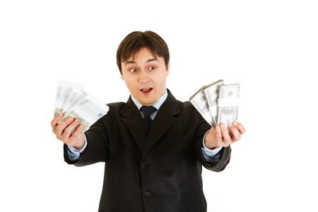 Surprised modern businessman holding money in his hand isolated on white  photo