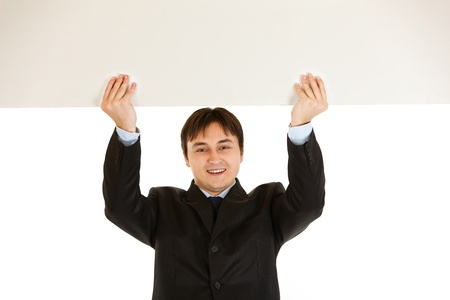 Smiling modern businessman holding blank billboard over head  photo