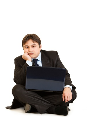 tedium: Bored businessman sitting on floor with laptop isolated on white