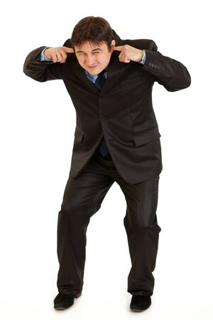 Businessman ducking in fear and closing ears with fingers isolated on white  photo