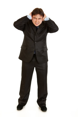 disgruntled: Annoyed businessman  closing ears with hands   isolated on white
