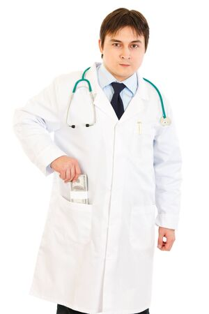 putting money in pocket: Serious medical doctor putting  money in pocket robe isolated on white