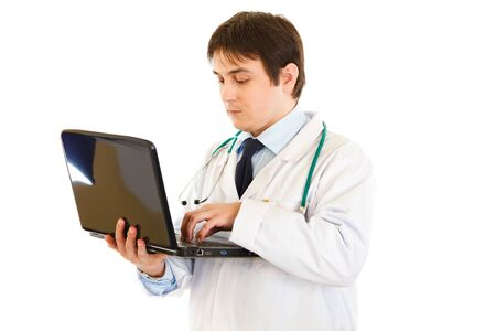 Serious medical doctor  working on laptop isolated on white