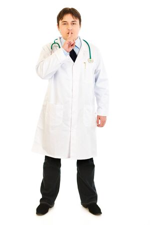 Serious  medical doctor with finger at mouth isolated on white. Shh gesture