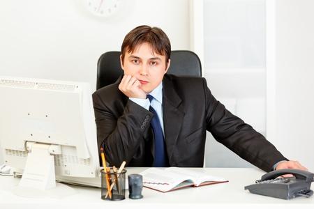 elegant business man: Thoughtful elegant business man sitting at desk in office  Archivio Fotografico