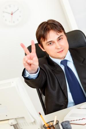 elegant business man: Smiling elegant business man sitting at office desk and showing victory gesture