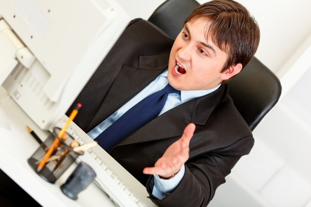 uptight: Stressful  modern businessman sitting at office desk and looking at computer monitor  Stock Photo