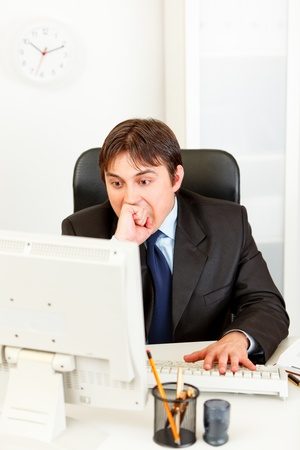 strenuous: Stressful modern businessman sitting at office desk and looking at computer monitor