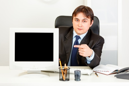 Authoritative  businessman sitting at office desk and pointing finger at  monitor with blank screen  photo