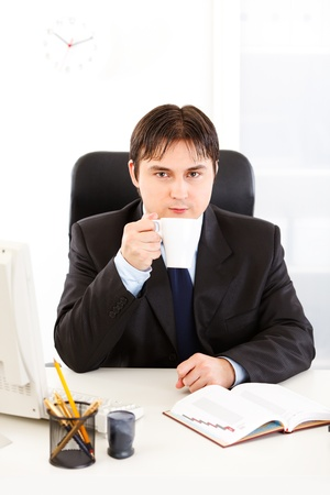 Modern business man sitting at office desk and drinking coffee  photo