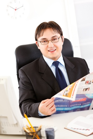 Smiling modern businessman sitting at office desk and holding newspaper in hands