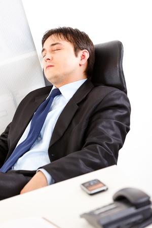 Tired modern businessman sleeping on office armchair  photo
