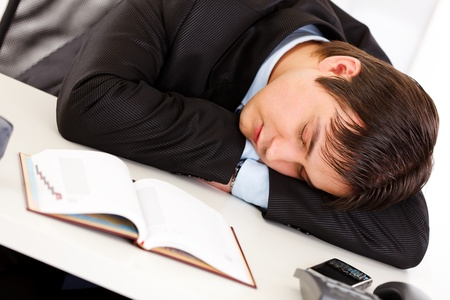 Tired businessman sleeping at  desk in  office   photo