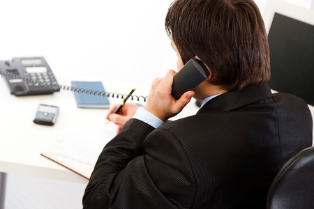 business costume: Modern businessman  in office talking on phone and making notes  in diary