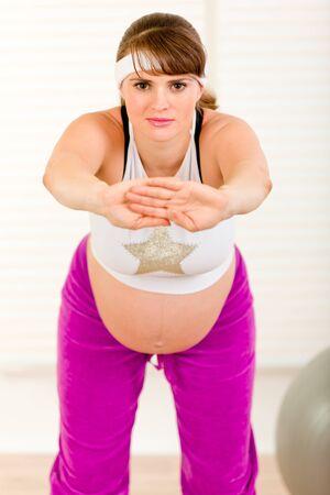 haciendo ejercicio: Atractiva mujer embarazada haciendo ejercicio en la sala de estar