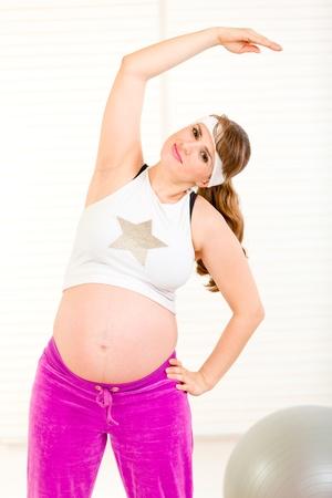 haciendo ejercicio: Sonriendo a bastante embarazada haciendo ejercicio en la sala de estar