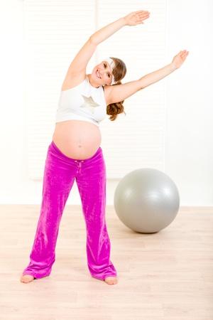 haciendo ejercicio: Sonrisa a encantadora mujer embarazada haciendo ejercicio en la sala de estar  Foto de archivo