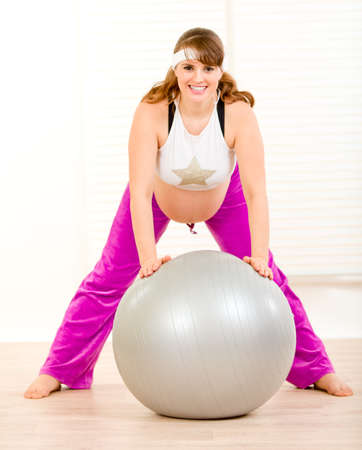 Smiling pretty pregnant woman doing exercises on fitness ball at living room  photo