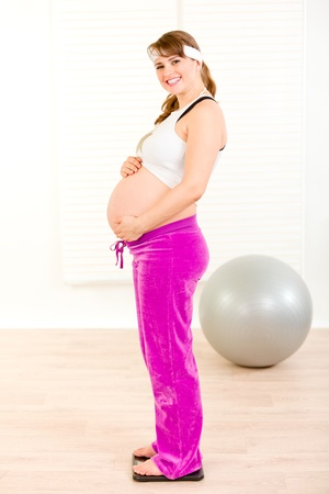 gewicht skala: Happy schwangere Frau stehend auf Waage und halten ihren Bauch  Lizenzfreie Bilder