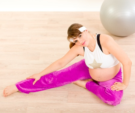 Smiling pretty pregnant woman doing stretching exercises Stock Photo - 9024607